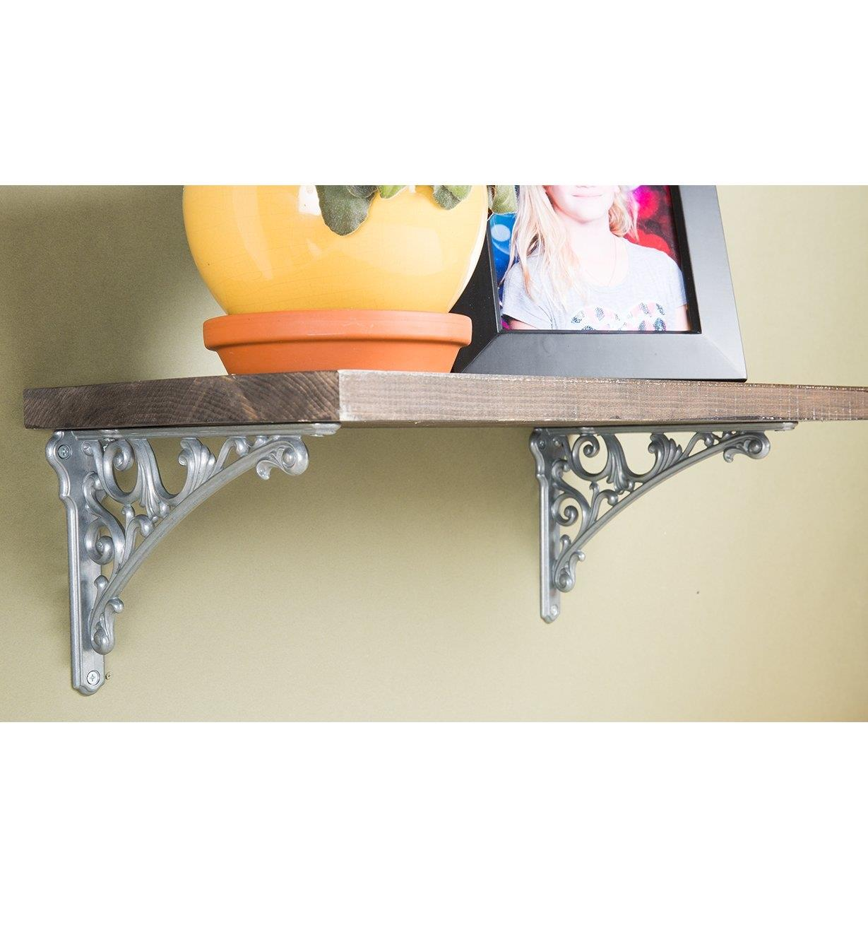 Two Classico Tumbled Nickel Shelf Brackets mounted to a shelf on a wall
