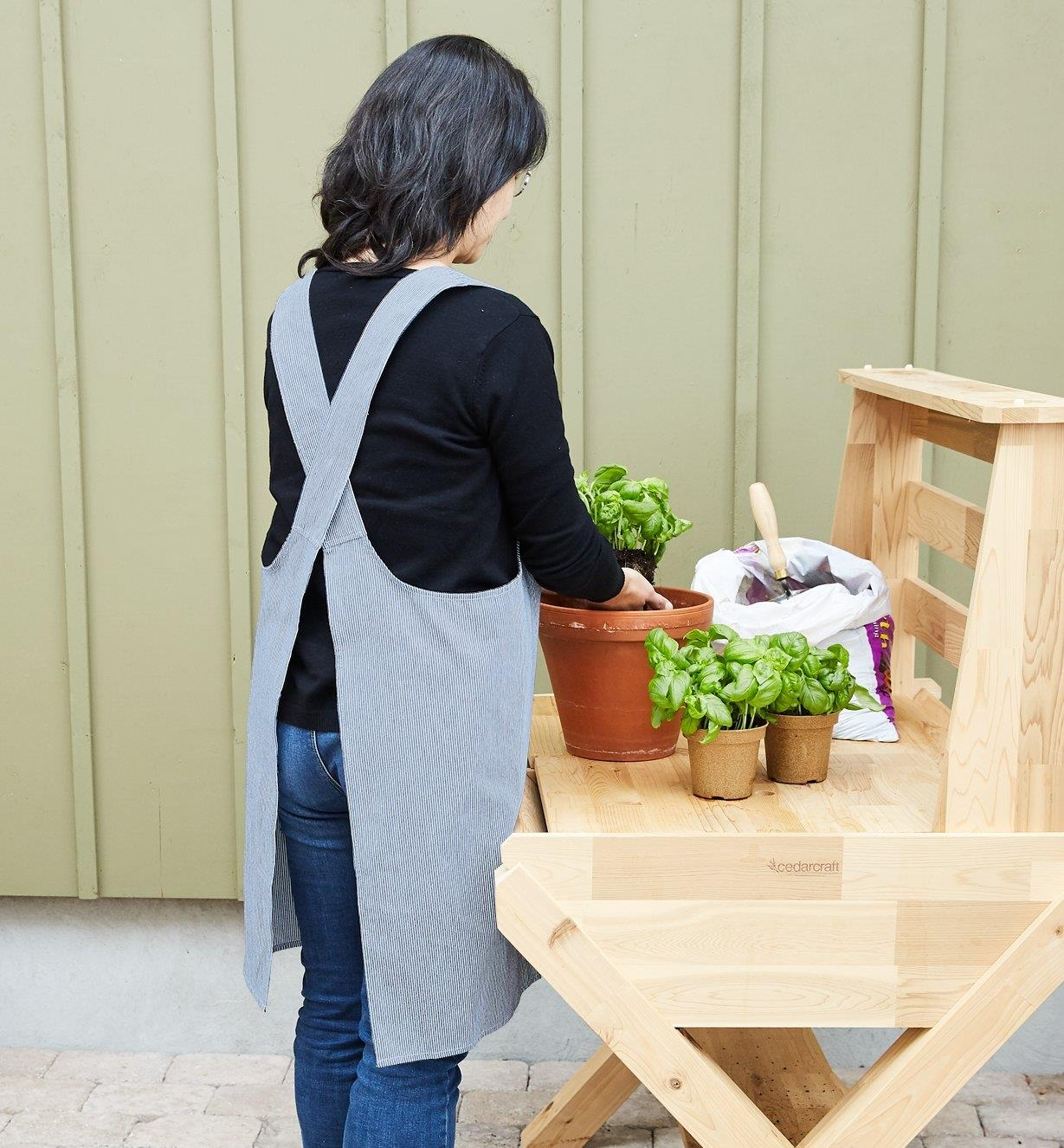 A woman wears a Cross-Back Apron while potting plants on a potting bench