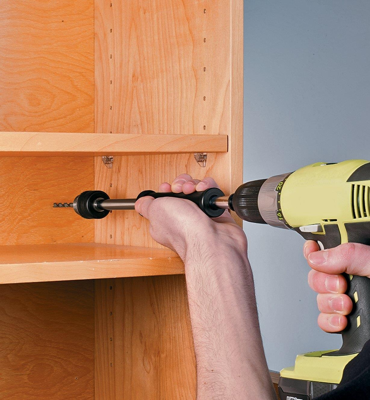 Drilling at the back of a bookcase using the Chuck Extender in an electric drill