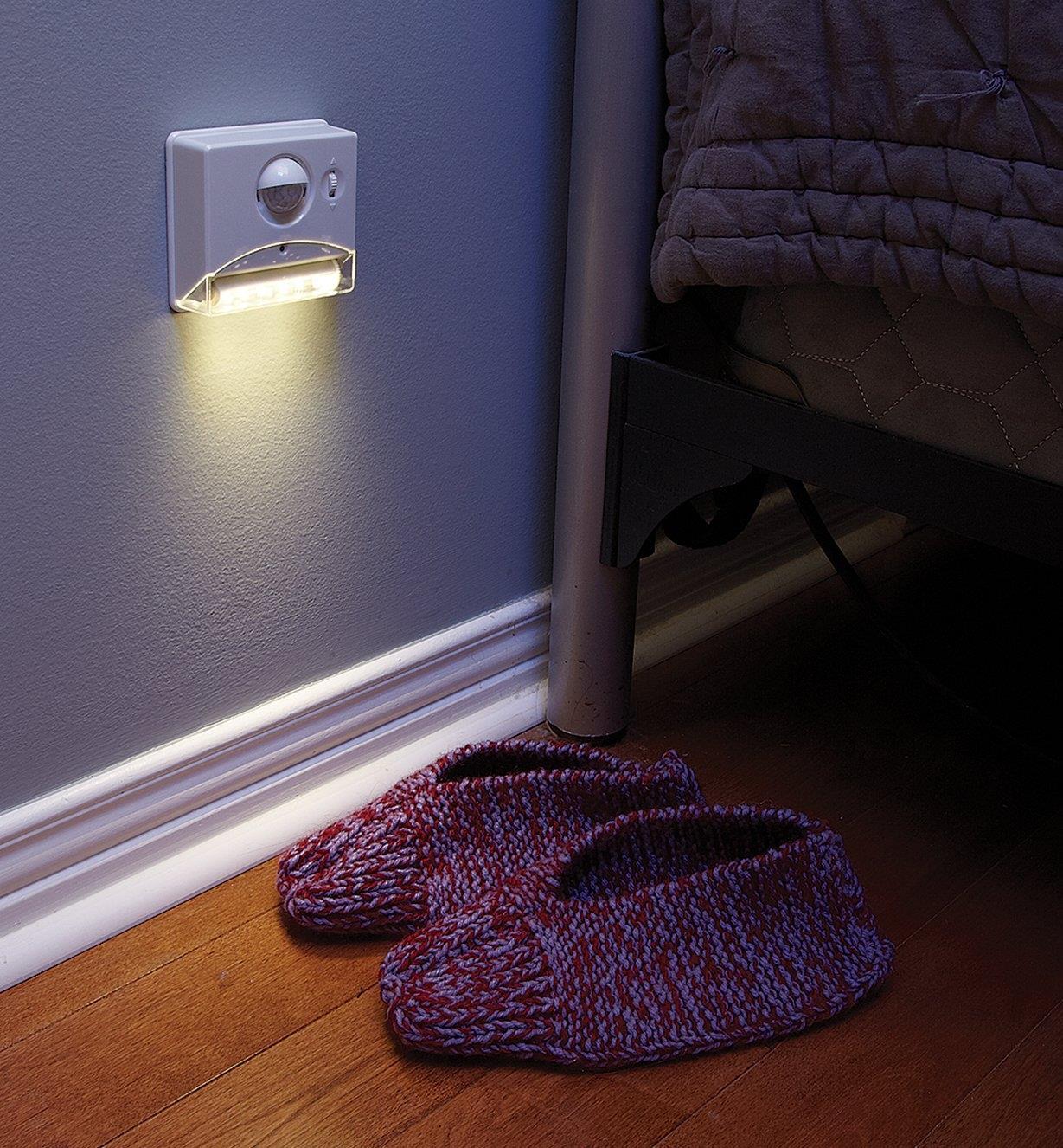 Lampe à détecteur infrarouge passif réglable posée sur un mur près du lit et éclairant une paire de pantoufles sur le plancher