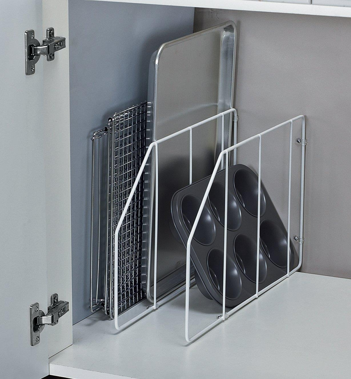 Baking pans separated between cabinet dividers installed in a cabinet