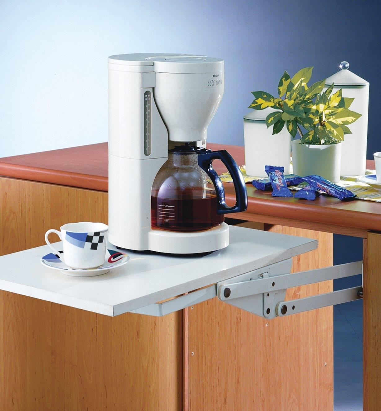 A swing-up shelf made with the Appliance Lift in the in-use position, holding a coffeemaker