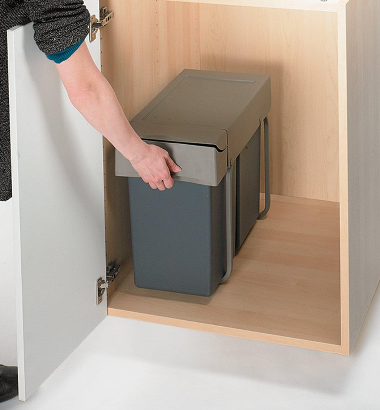 Gripping the Waste Container to slide it out of the cabinet