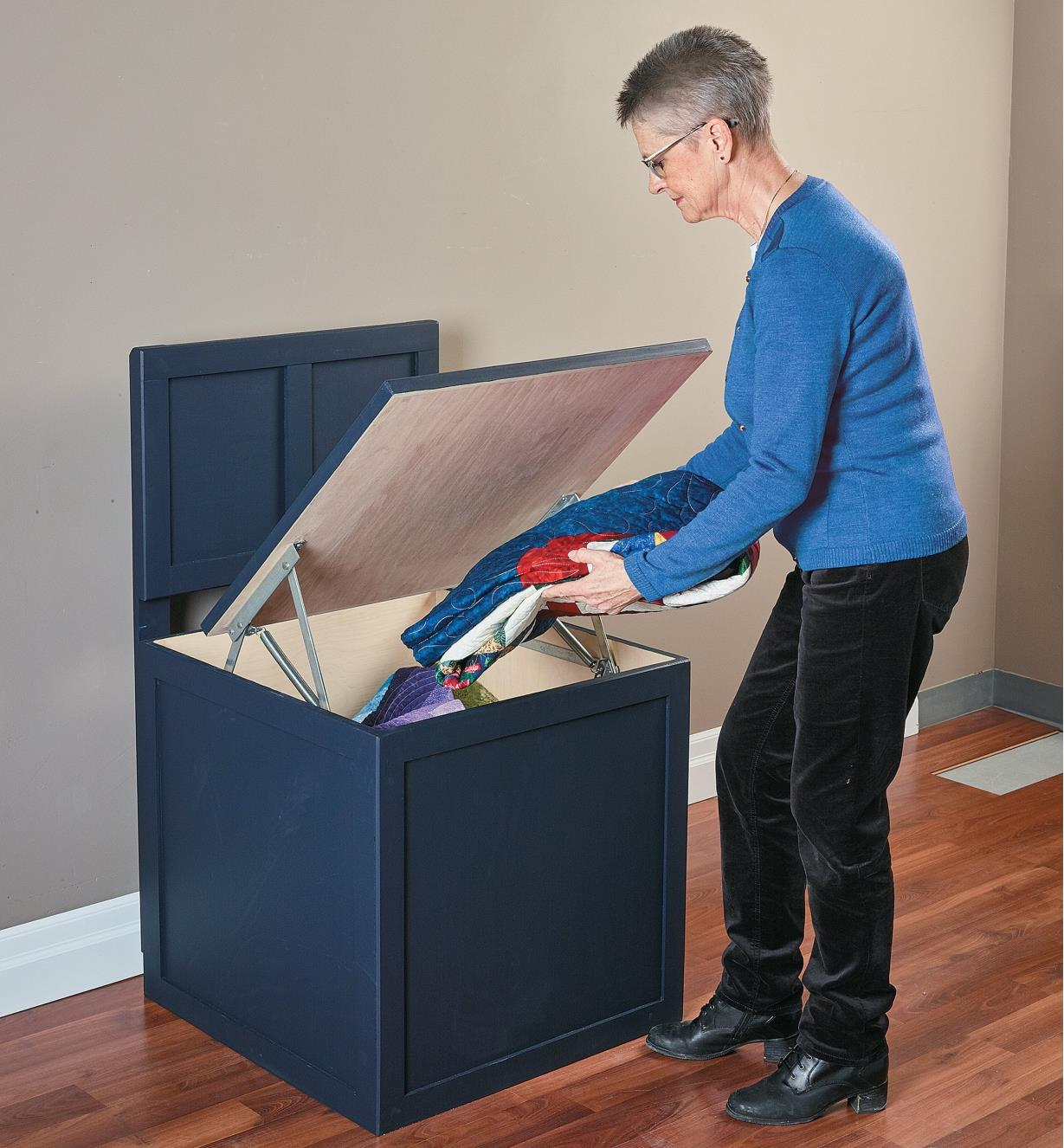 A woman places blankets inside a bench seat storage box made with the Bench Seat Hinges