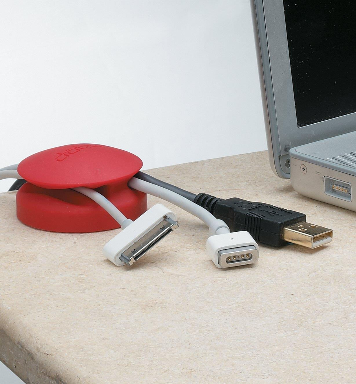 A Cord Catcher on a desk with three cables in the channels