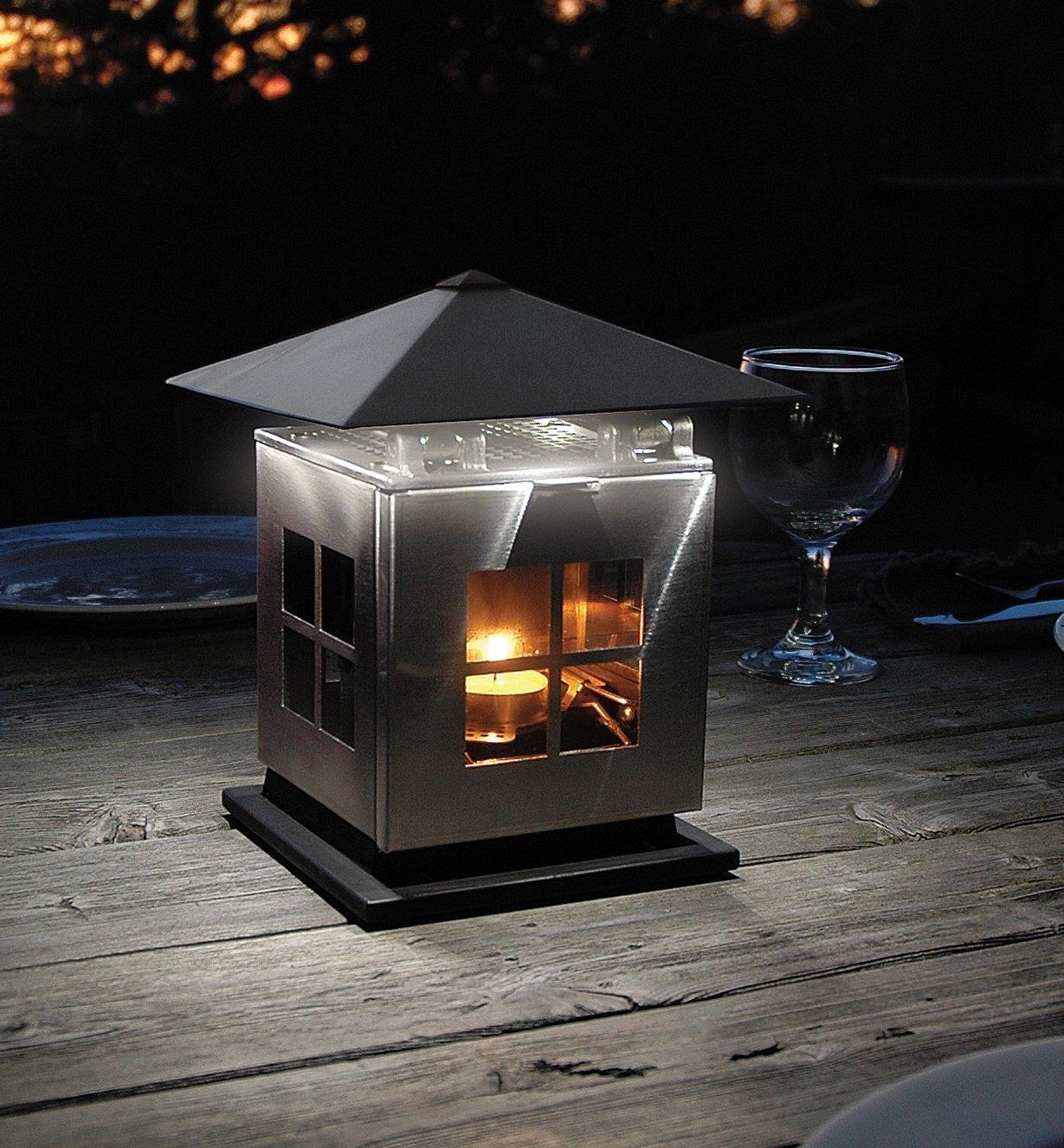 Lanterne à DEL alimentée par bougie posée sur une table d'extérieur avec le petit toit abaissé pour éclairer une zone limitée