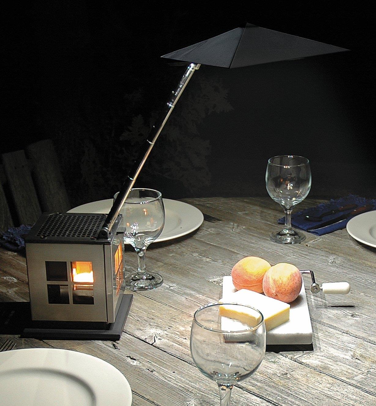 Lanterne à DEL alimentée par bougie posée sur une table d'extérieur avec le petit toit abaissé pour éclairer une large zone