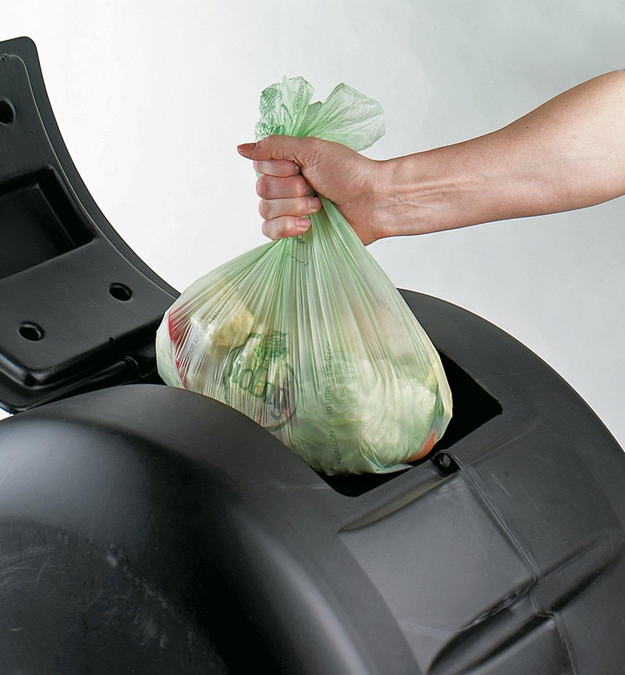 Placing a full compostable bag inside a compost bin