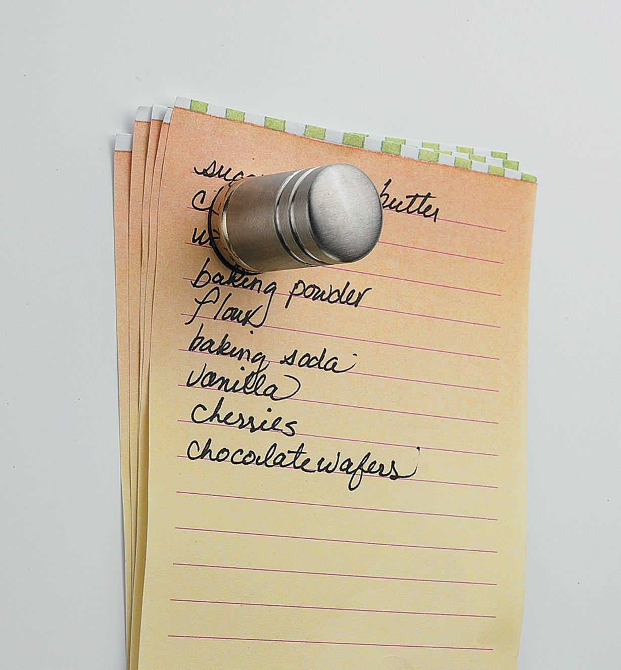 Example of customized magnet holding a shopping list on a fridge
