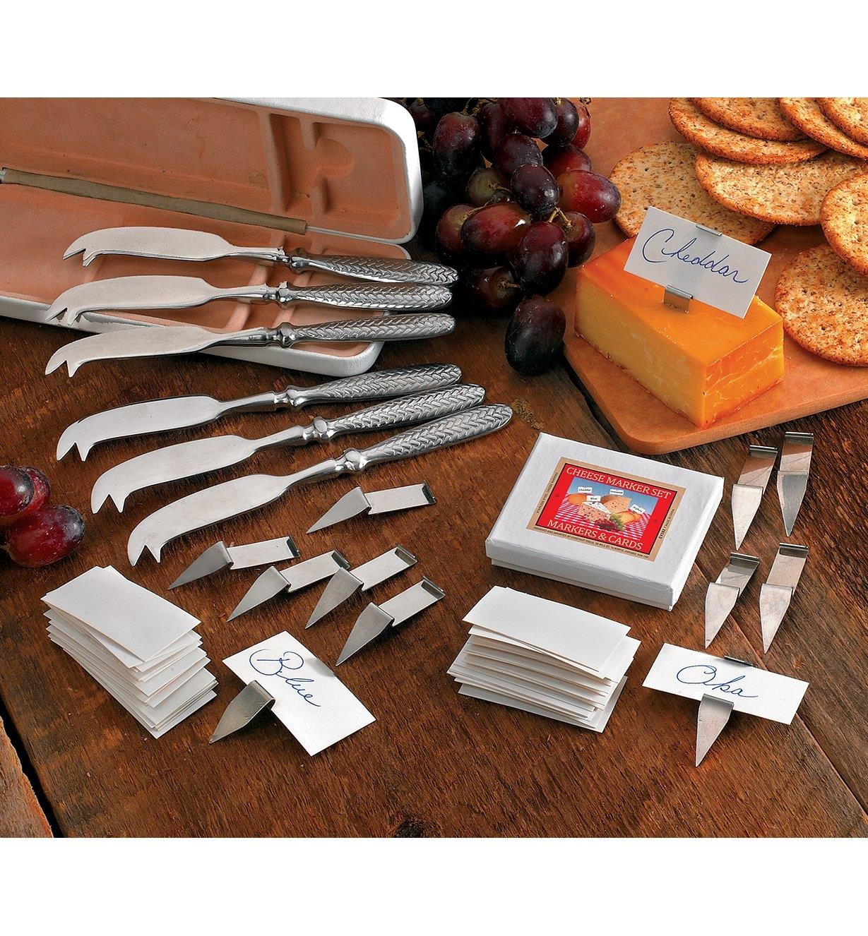 Cheese Knife and Marker Set spread out on a table beside a platter of cheese, crackers and grapes