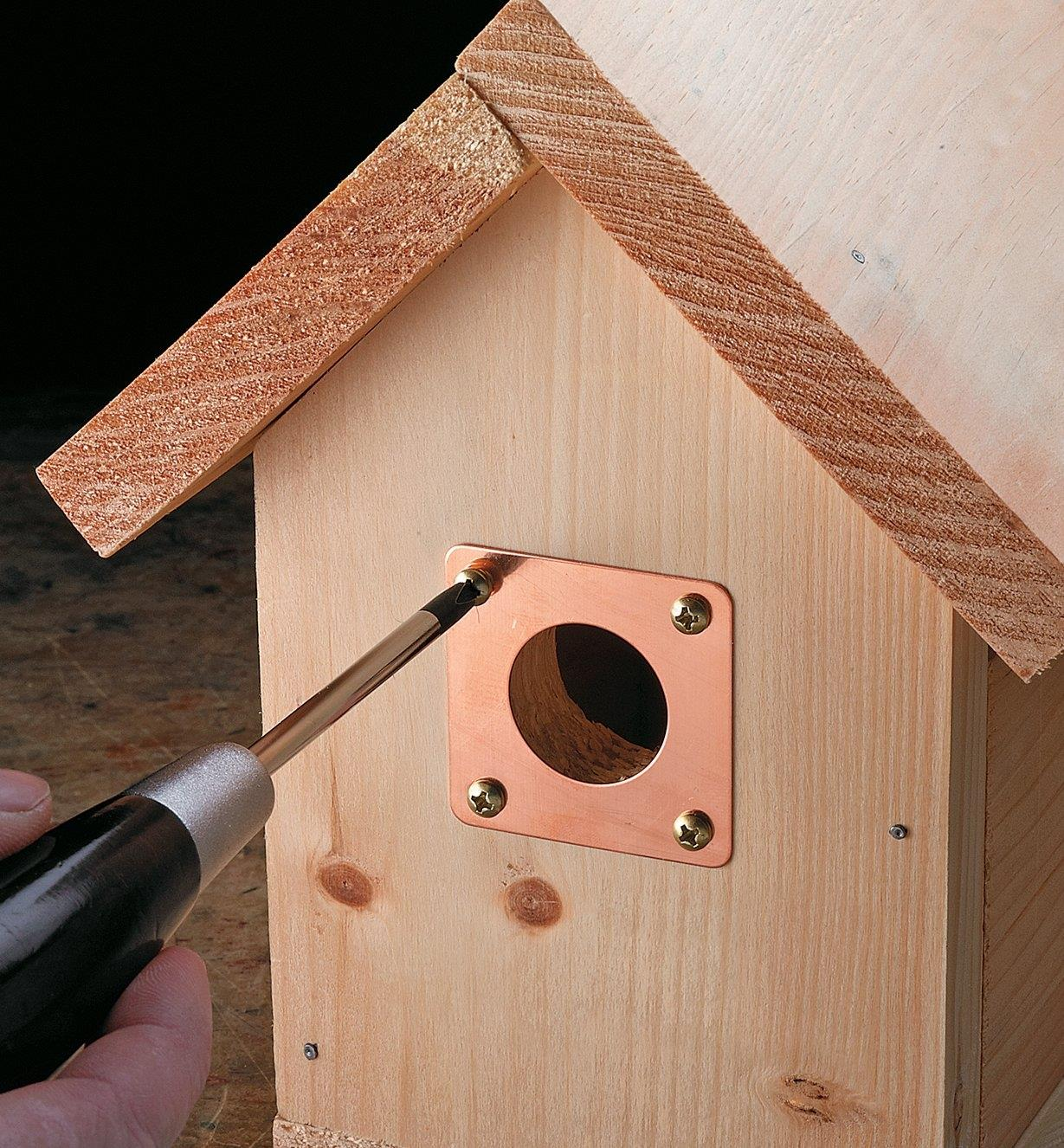 Using a screwdriver to install a portal protector on a birdhouse