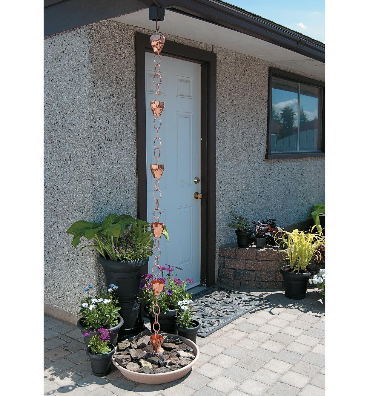Two connected 3' sections of copper rain chain hang between a downspout opening and a splash plate