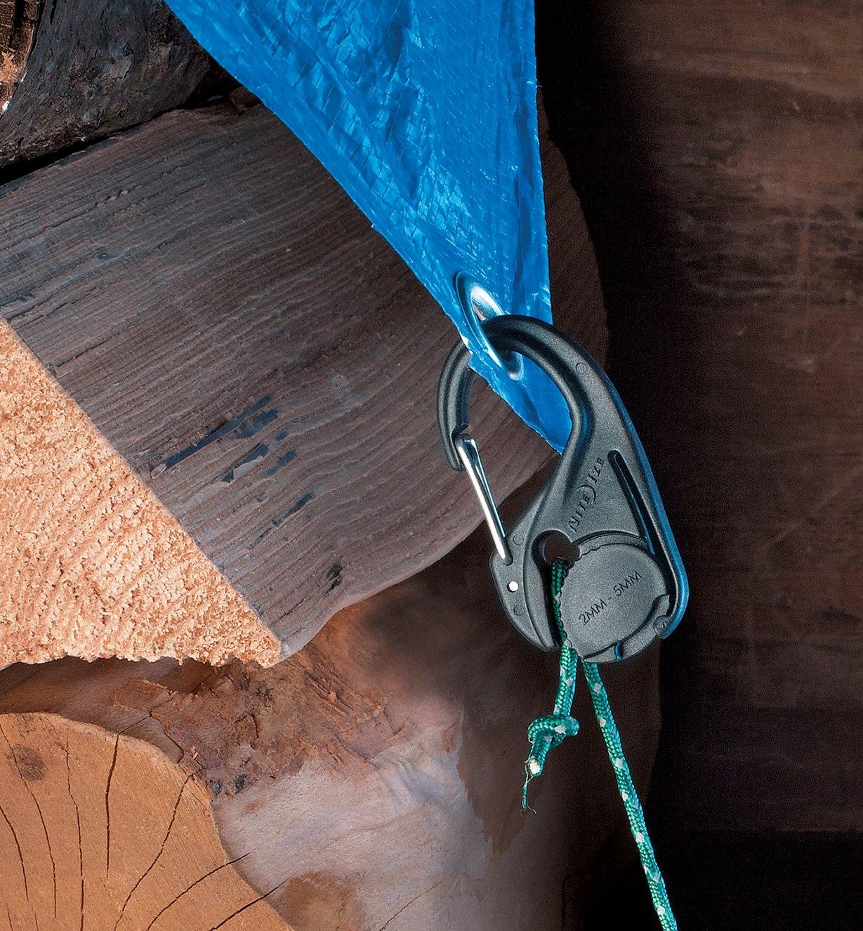 Nylon CamJam Cord Tightener holding a tarp over a woodpile