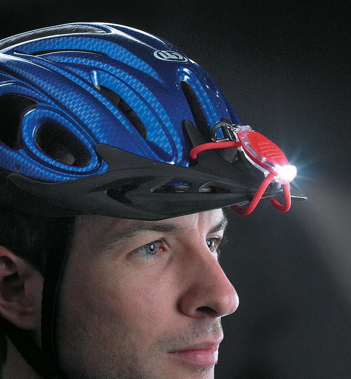 A man wears a Red BugLit LED Micro-Light on the peak of a bike helmet