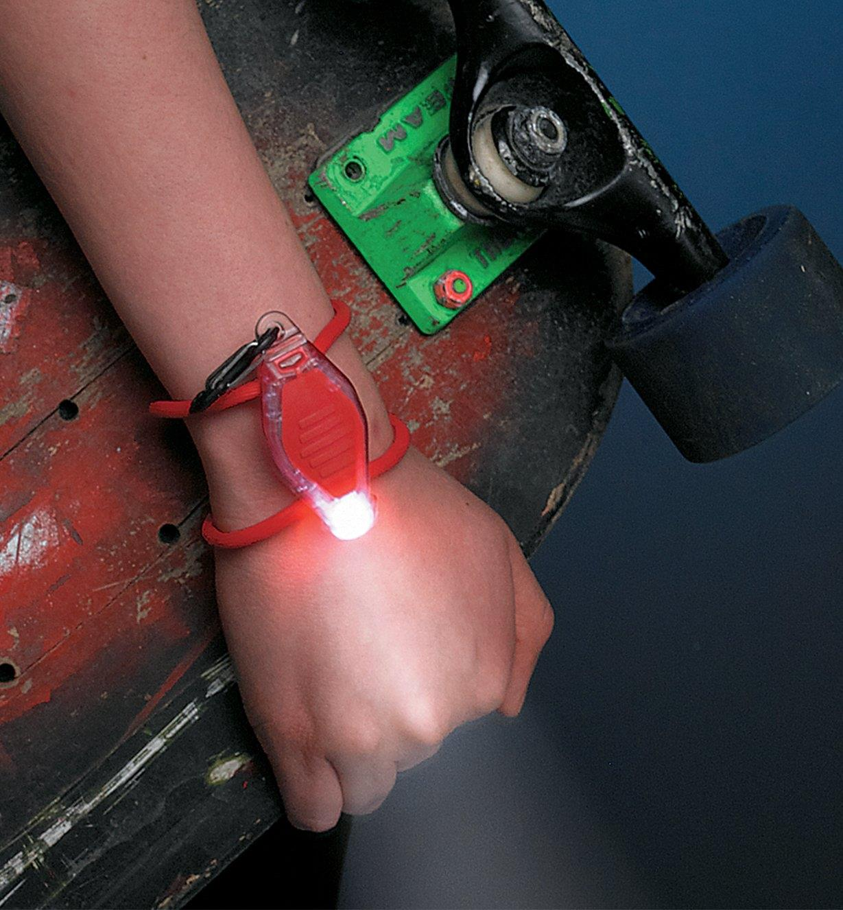 A youth wears a Red BugLit LED Micro-Light on their wrist while carrying a skateboard