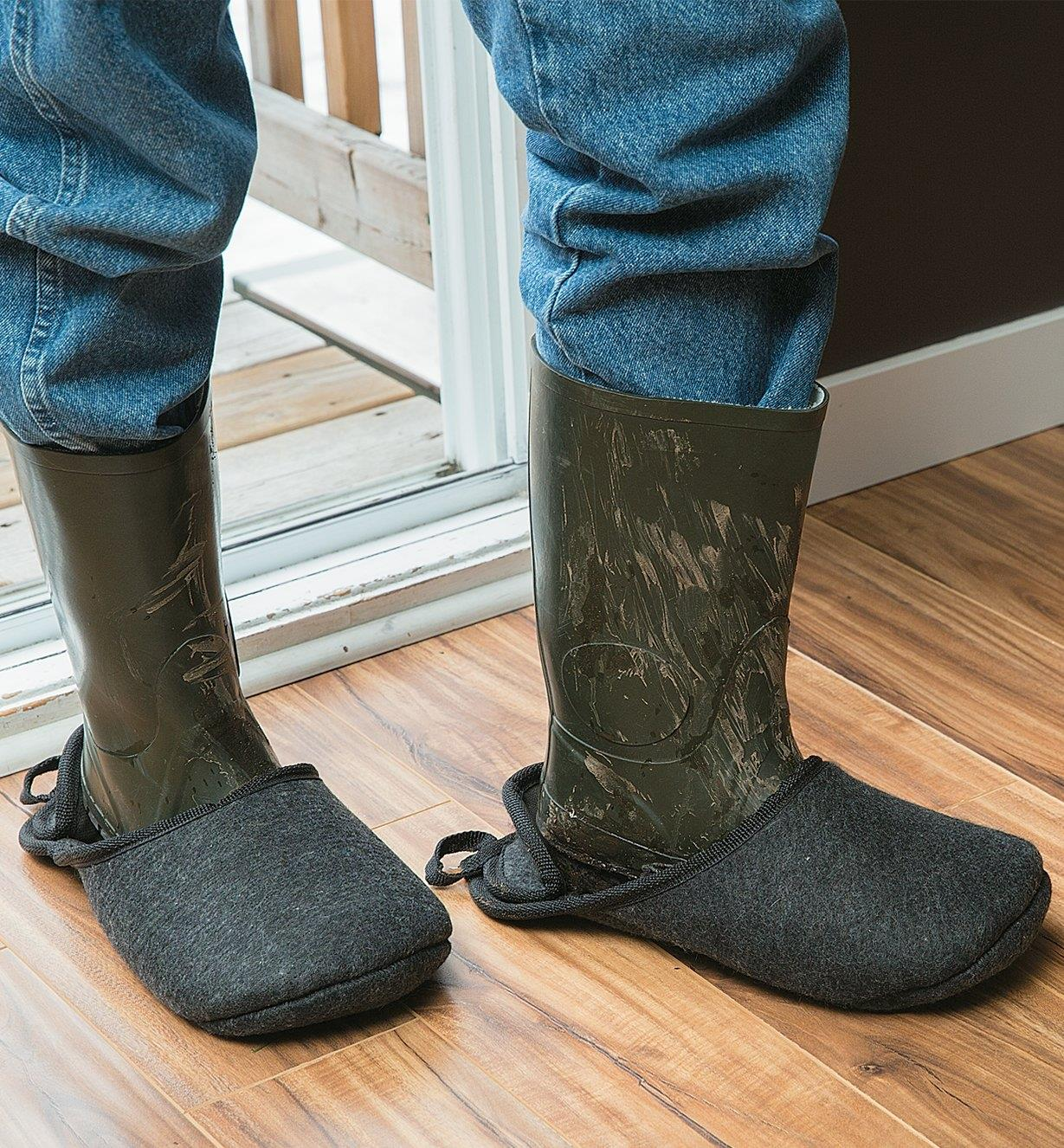 Boot slippers worn over a pair of muddy boots inside a doorway