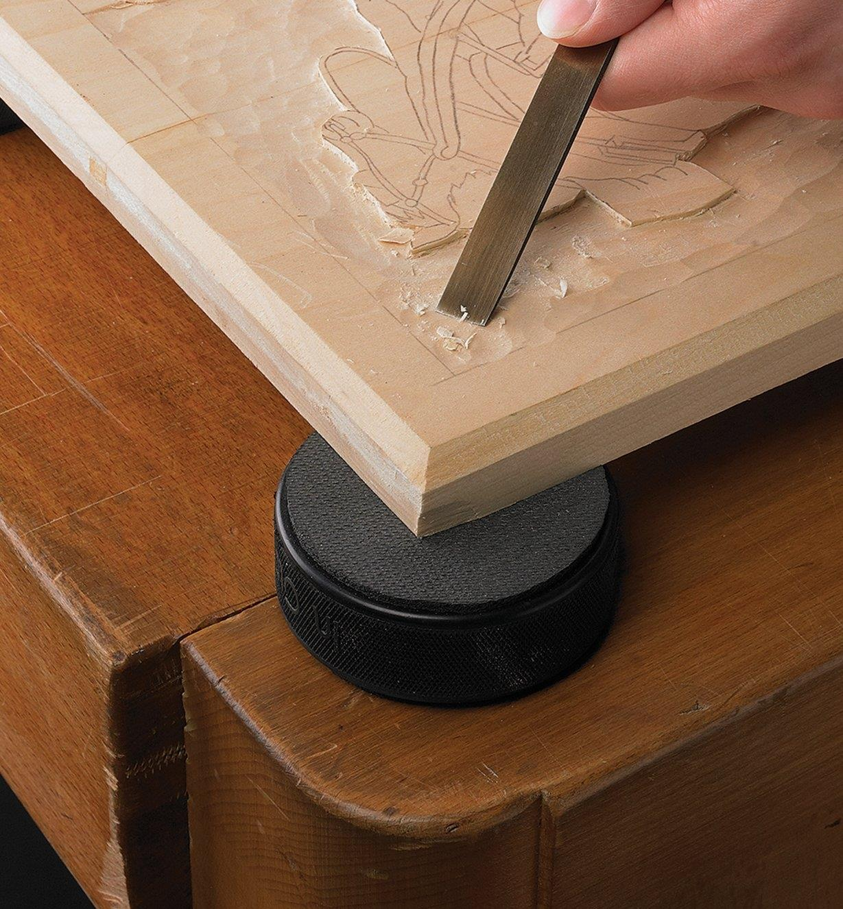 Grip disc attached to a hockey puck, used as a work standoff under a relief carving