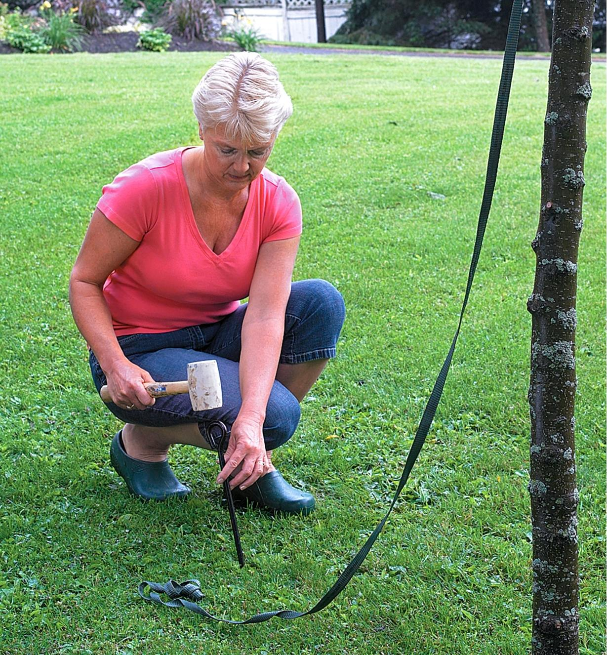 A woman uses arbor tape to stake a young tree