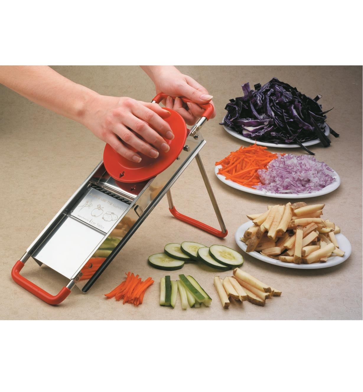 Slicing vegetables with the Classic French Mandoline, with plates of various sliced veggies nearby