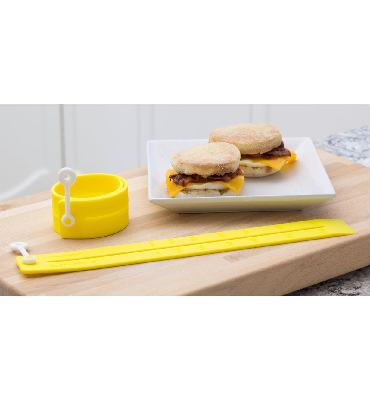 Two Adjustable Silicone Egg Rings beside two breakfast sandwiches made with eggs, bacon and cheese