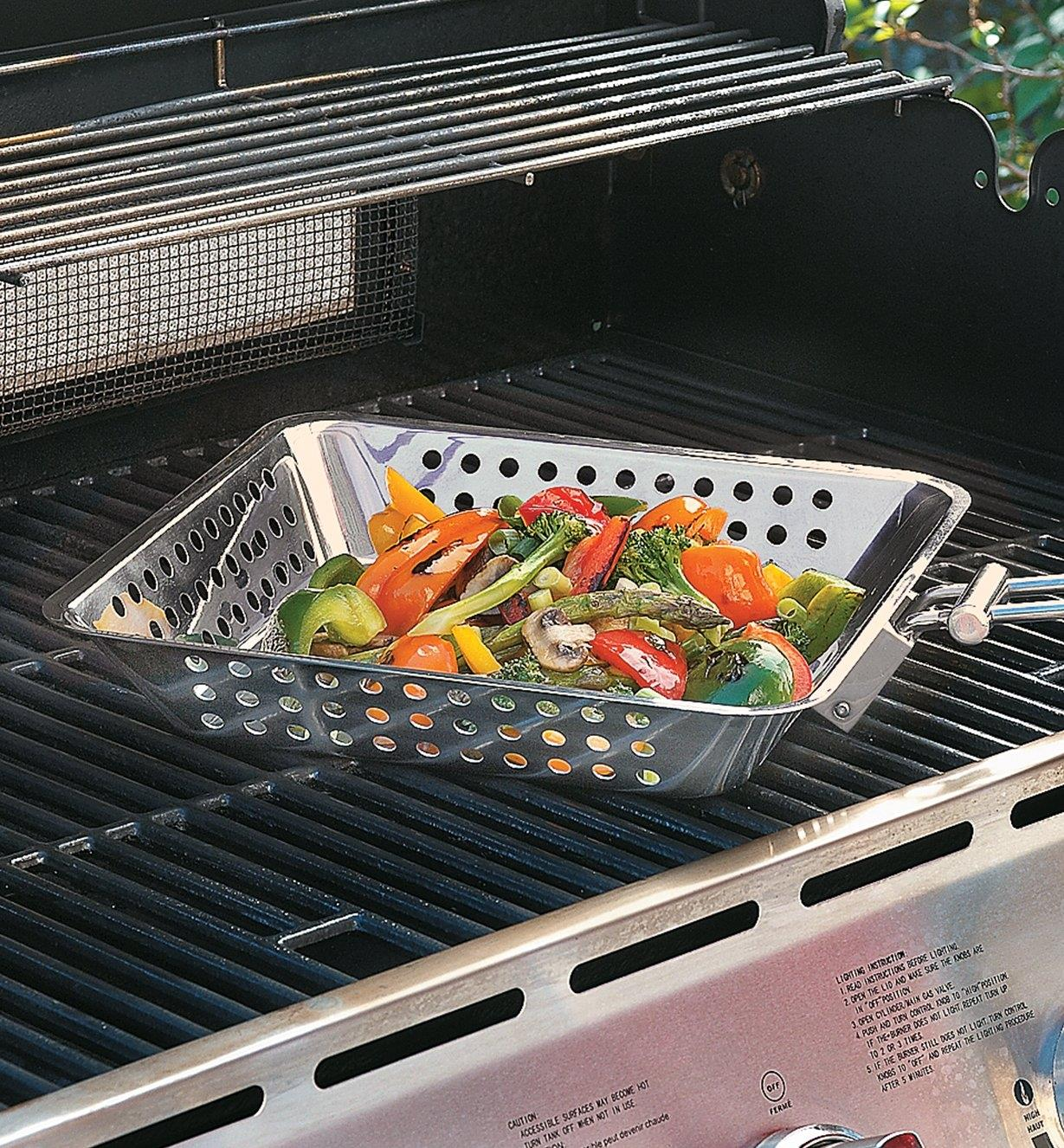 Barbecue Grilling Basket sitting on a grill, filled with vegetables