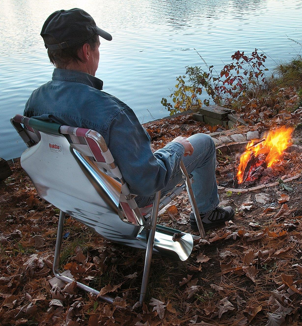 A man sitting in a lawn chair with the Campfire Back Warmer attached