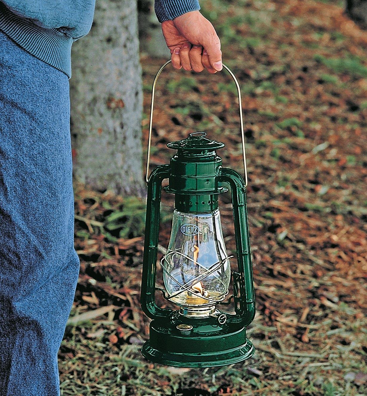 Personne tenant une lampe-tempête Dietz n° 80 par l'anse