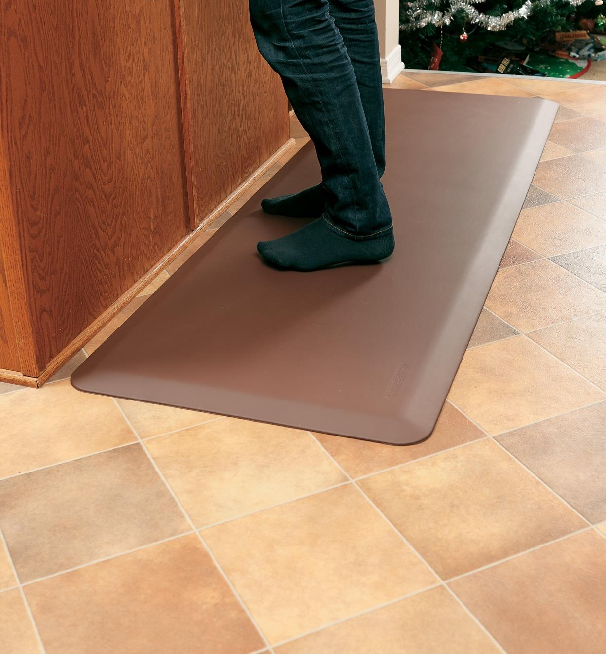 "A person standing on a 24"" x 72"" brown Stationary Mat by a counter"