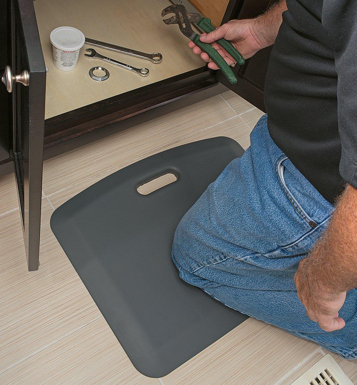 """A man kneels on an 18"""" x 22"""" gray Portable Mat by an open cupboard"""
