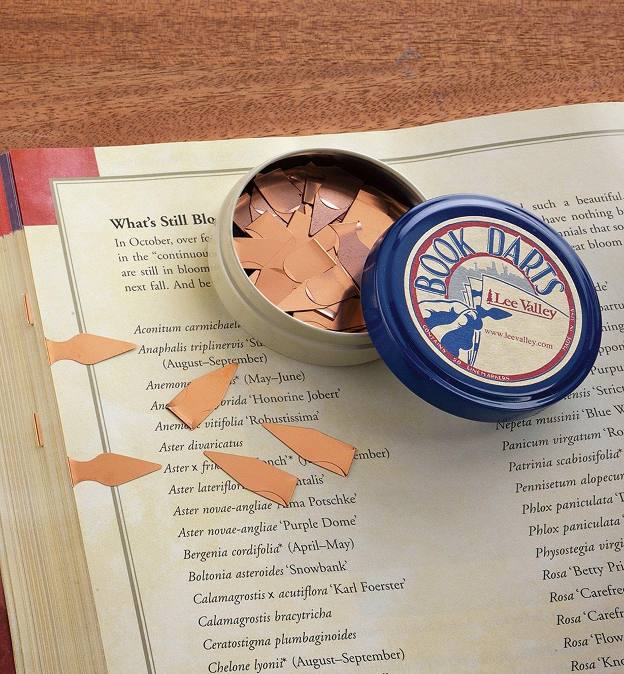 A tin of Book Darts sitting on an open book with two darts clipped to the page