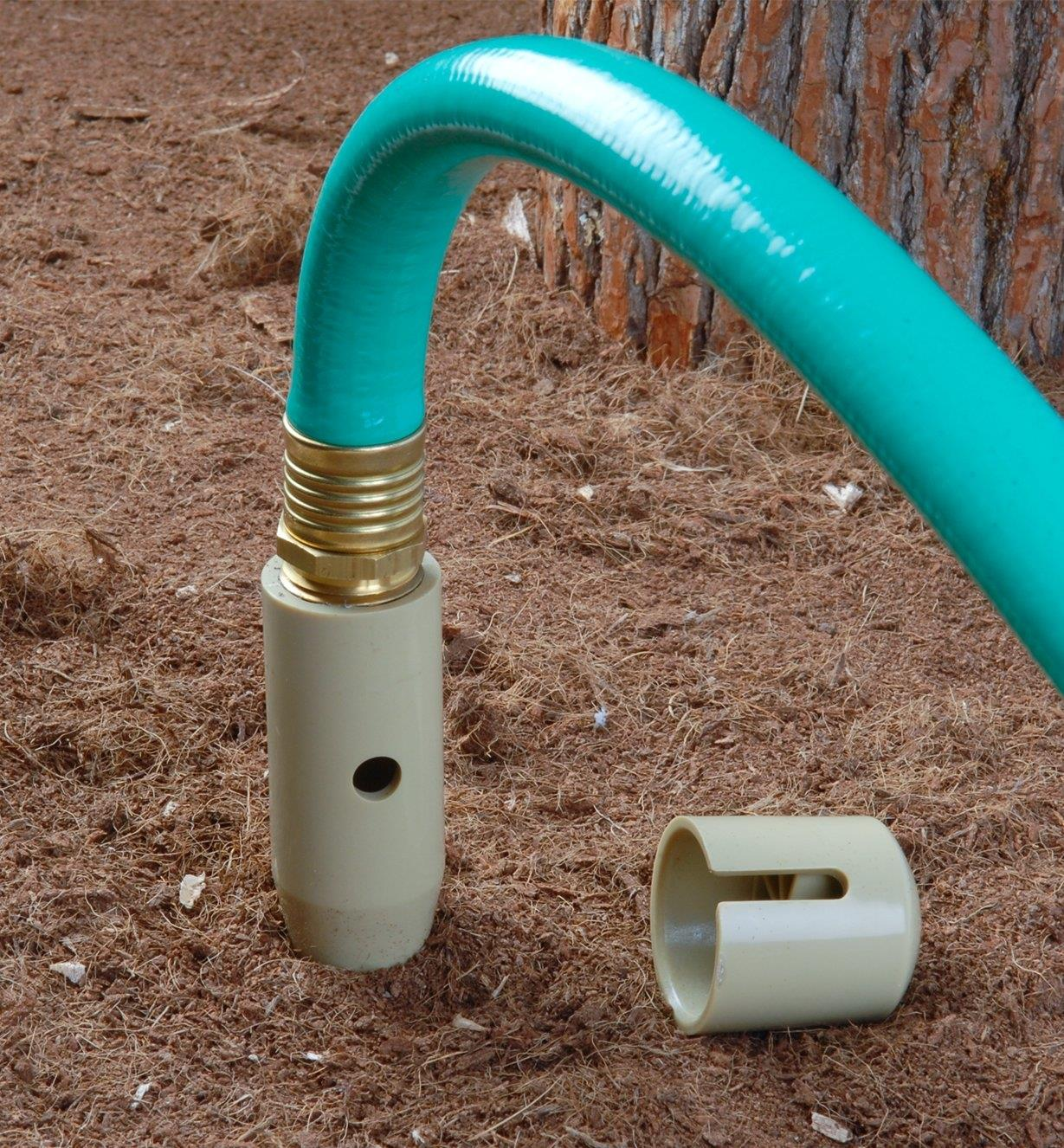 Deep Drip Watering Spike inserted into the ground, attached to a garden hose