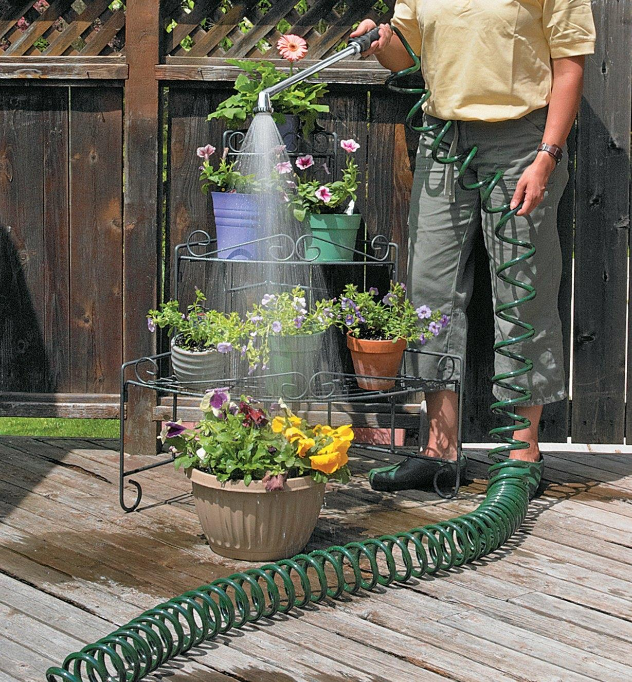 Using the Deluxe Watering Set to water potted plants on a plants stand