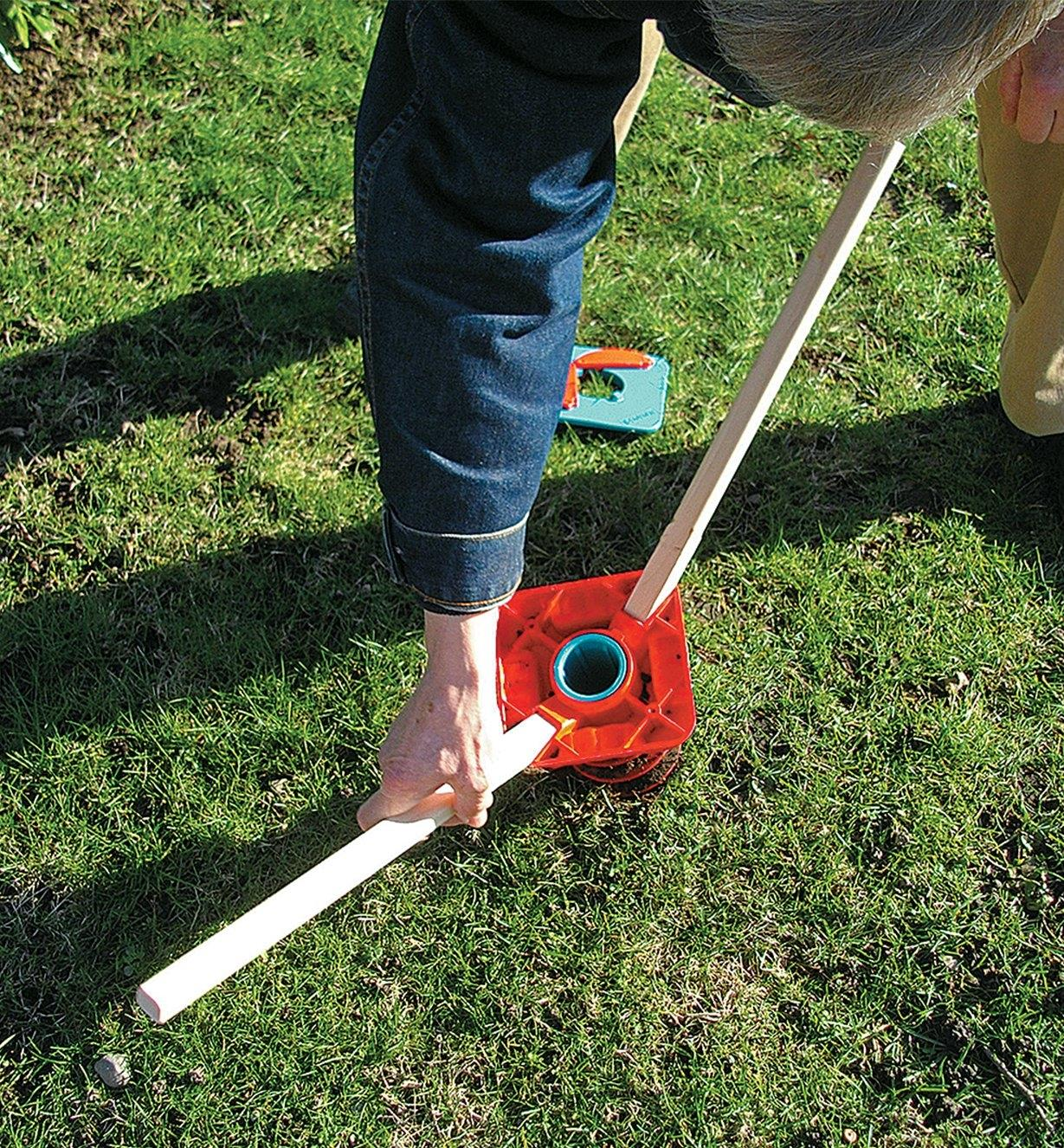 Installing the ground screw by twisting it into the ground using two rods