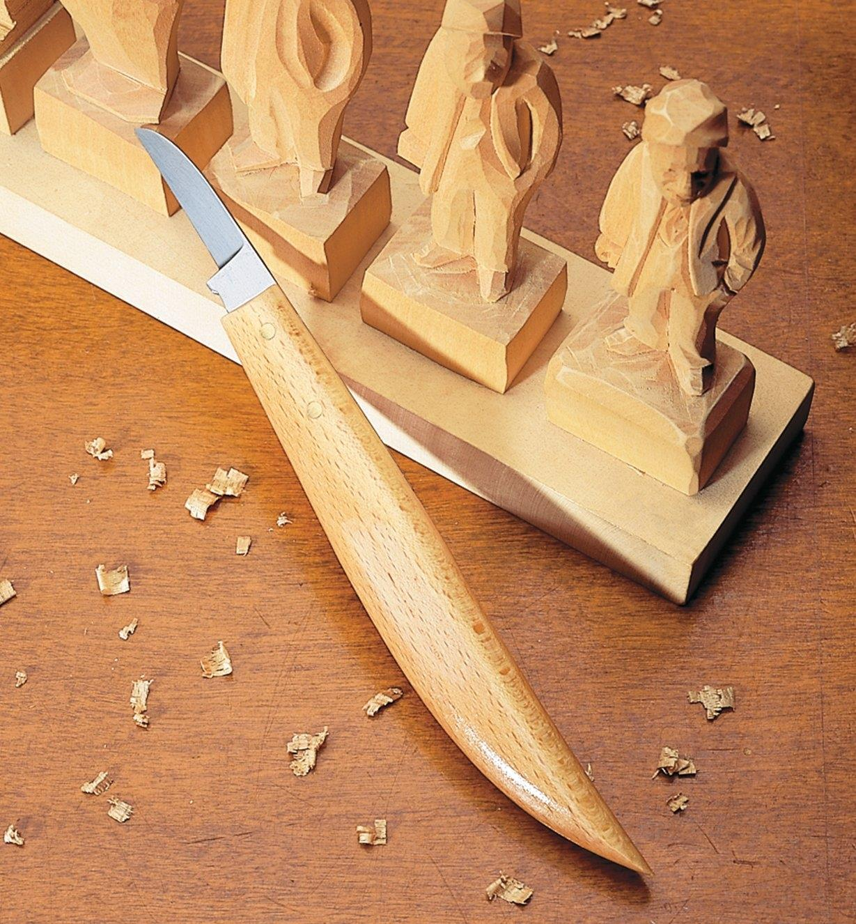 Chip Knife #8 placed next to a series of carved figurines