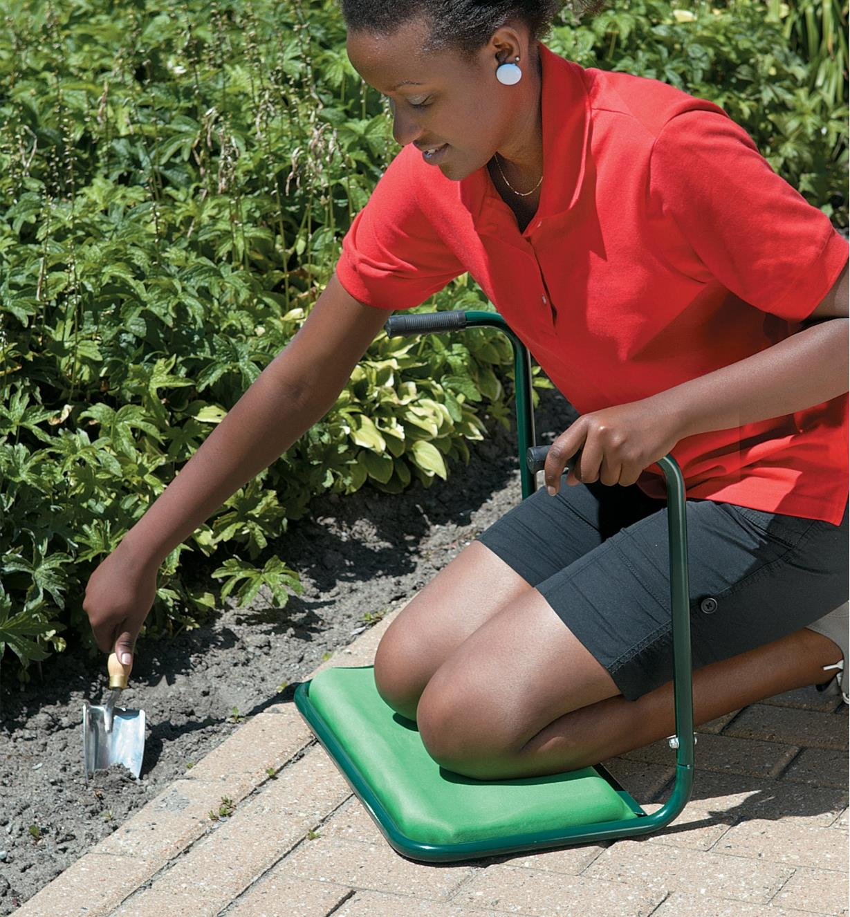 A woman kneels on the Garden Kneeler while gardening