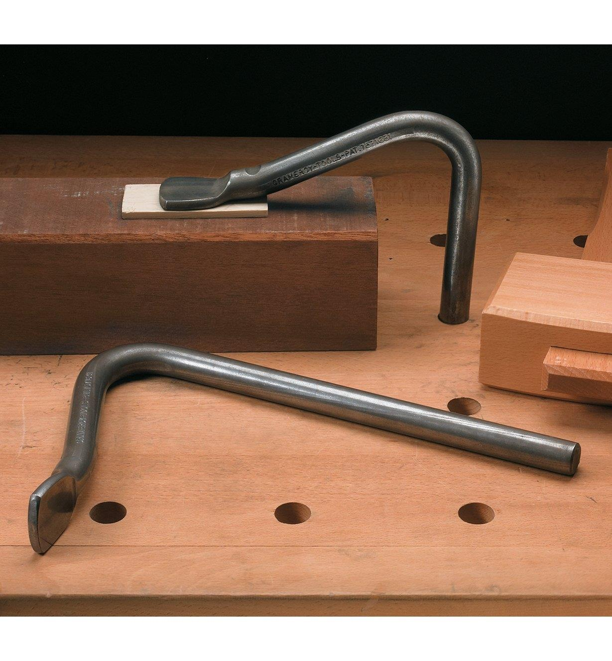 One holdfast lying on a workbench and the other inserted in a dog hole, holding a workpiece