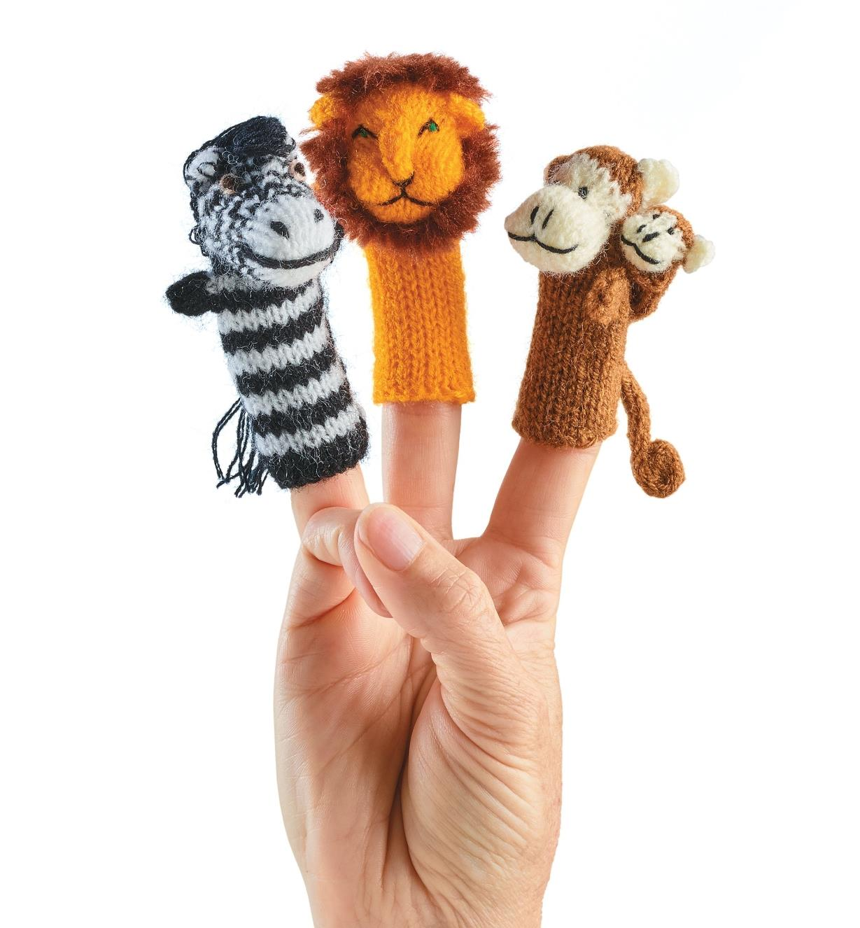 Zebra, lion and monkey from safari finger puppets on a person's hand