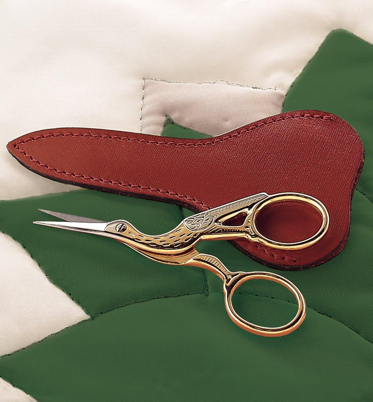 Stork Scissors and Sheath lying on a quilt
