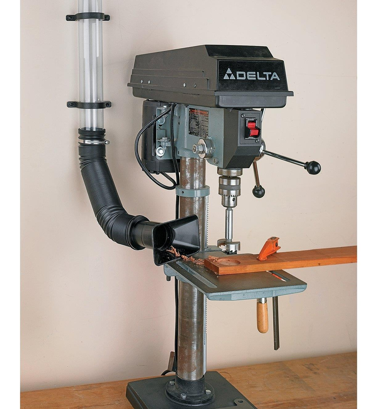 Expandable Vacuum Hose and nozzle collecting dust from a drill press table