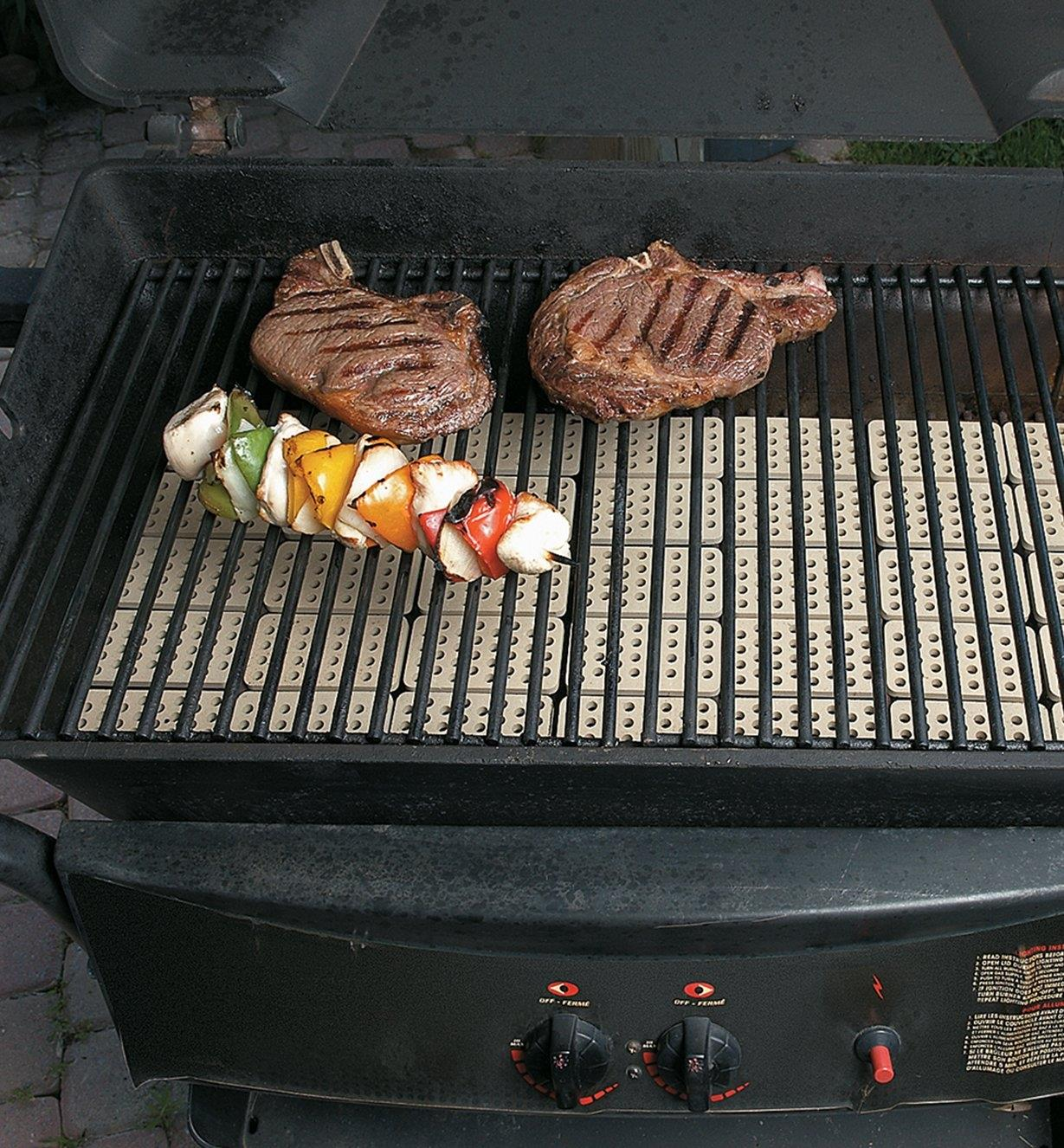 Grill Tiles in place on a barbecue where food is cooking
