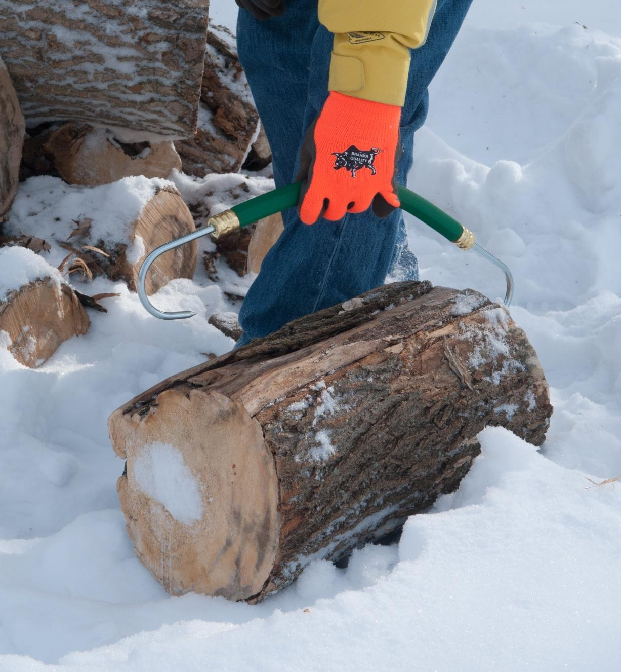 Firewood Gripper being hooked into the ends of a log for carrying
