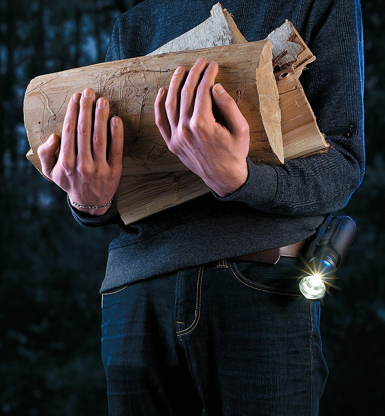 A person with a flashlight in a holster secured to their belt, carrying an armload of firewood