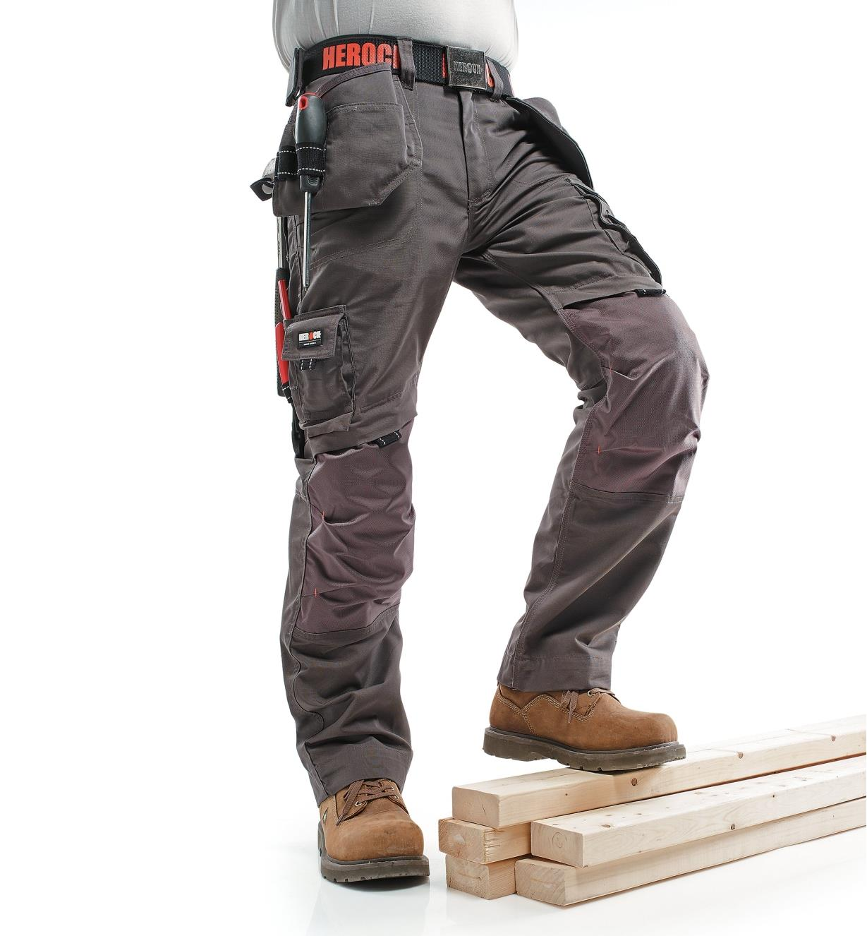 A man poses in Gray Medium-Weight Pants with his foot on a stack of lumber