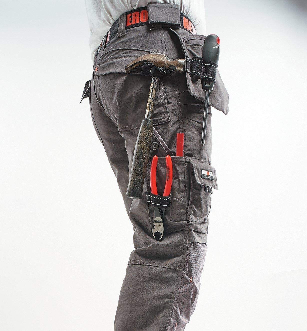 Side view of gray pants with various tools in the loops and pockets
