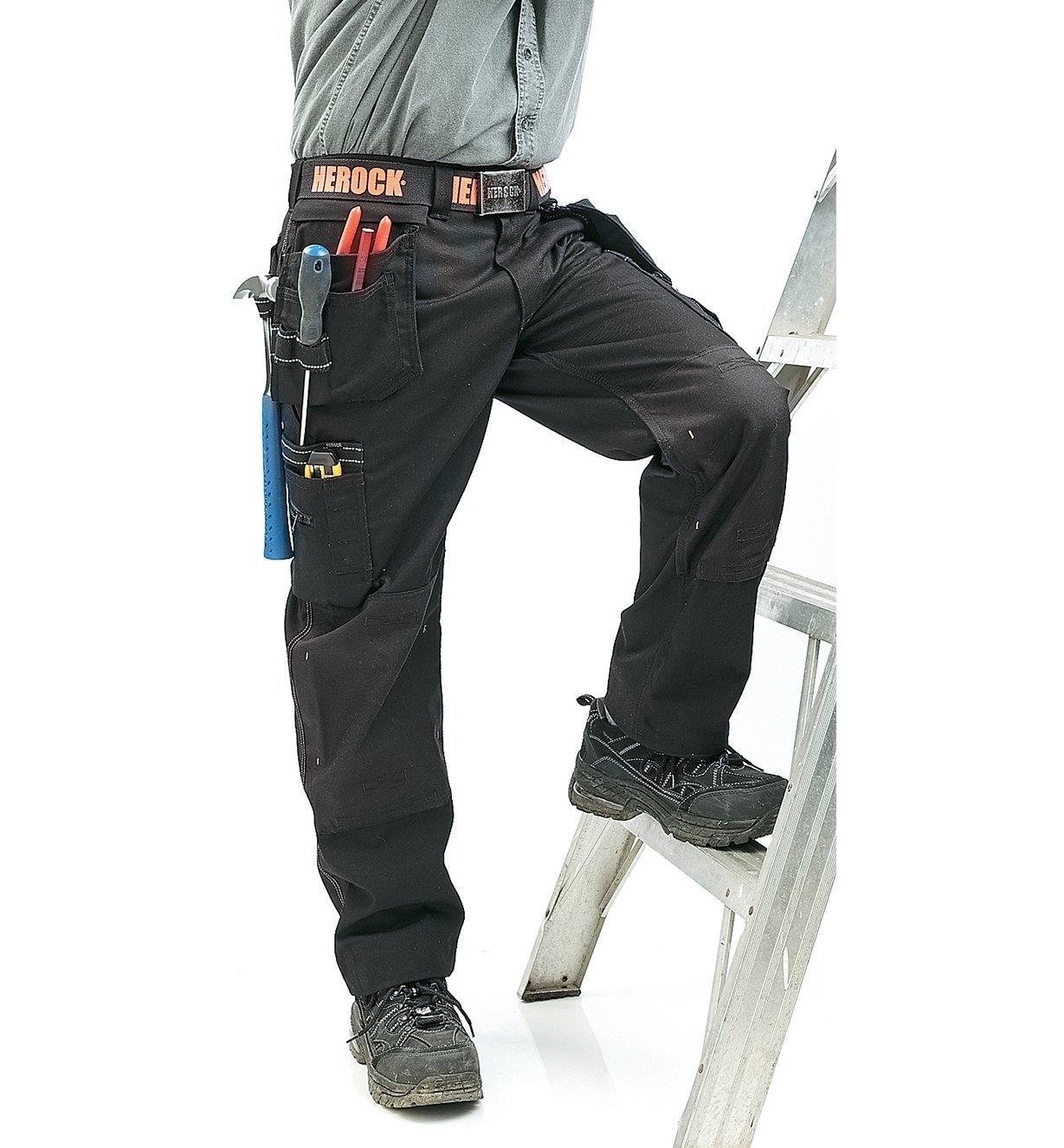 A man wearing Black Heavyweight Pants climbs a ladder