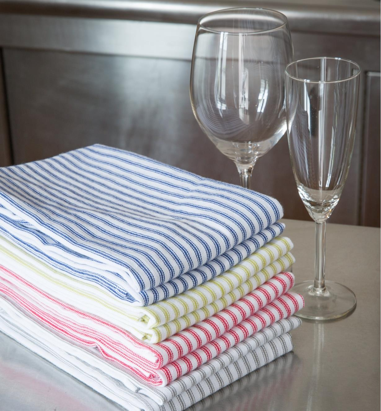 A stack of eight folded Glass Towels beside a wine glass and a champagne glass