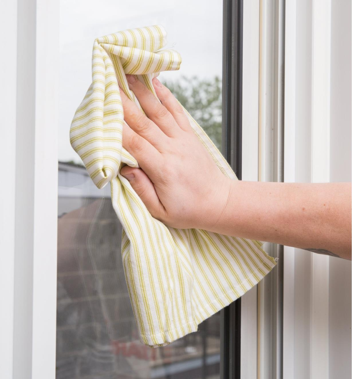 Wiping a windowpane with a Green Stripe Glass Towel