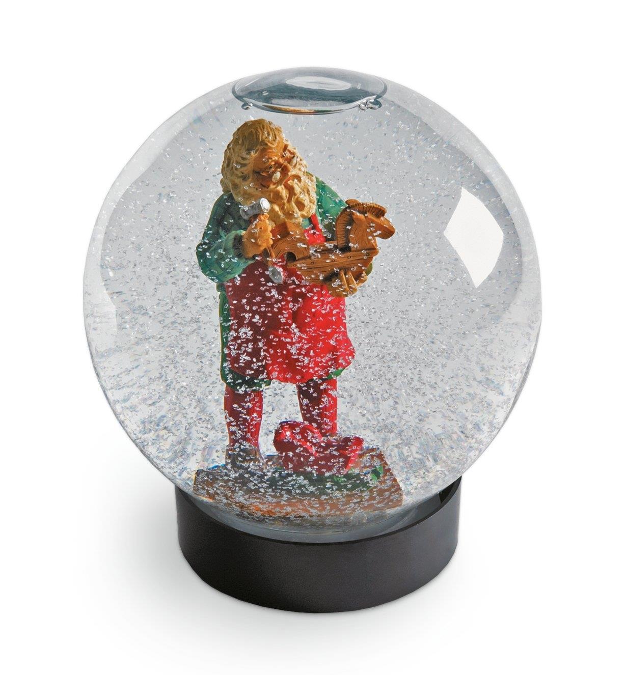 Figurine du père Noël et neige artificielle dans un aquarium pour fleurs rempli d'eau