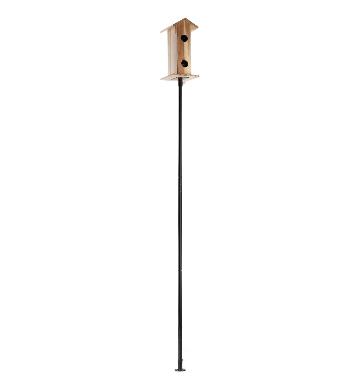 Birdhouse mounted on a flange-top garden pole