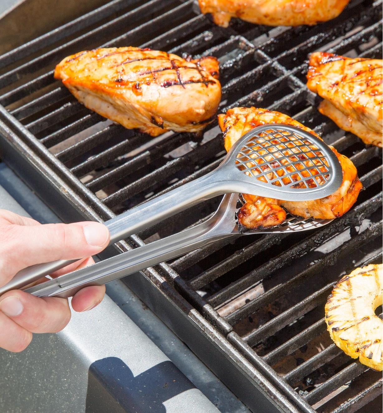 Using Grill Fry Tongs to pick up a chicken breast on a barbecue